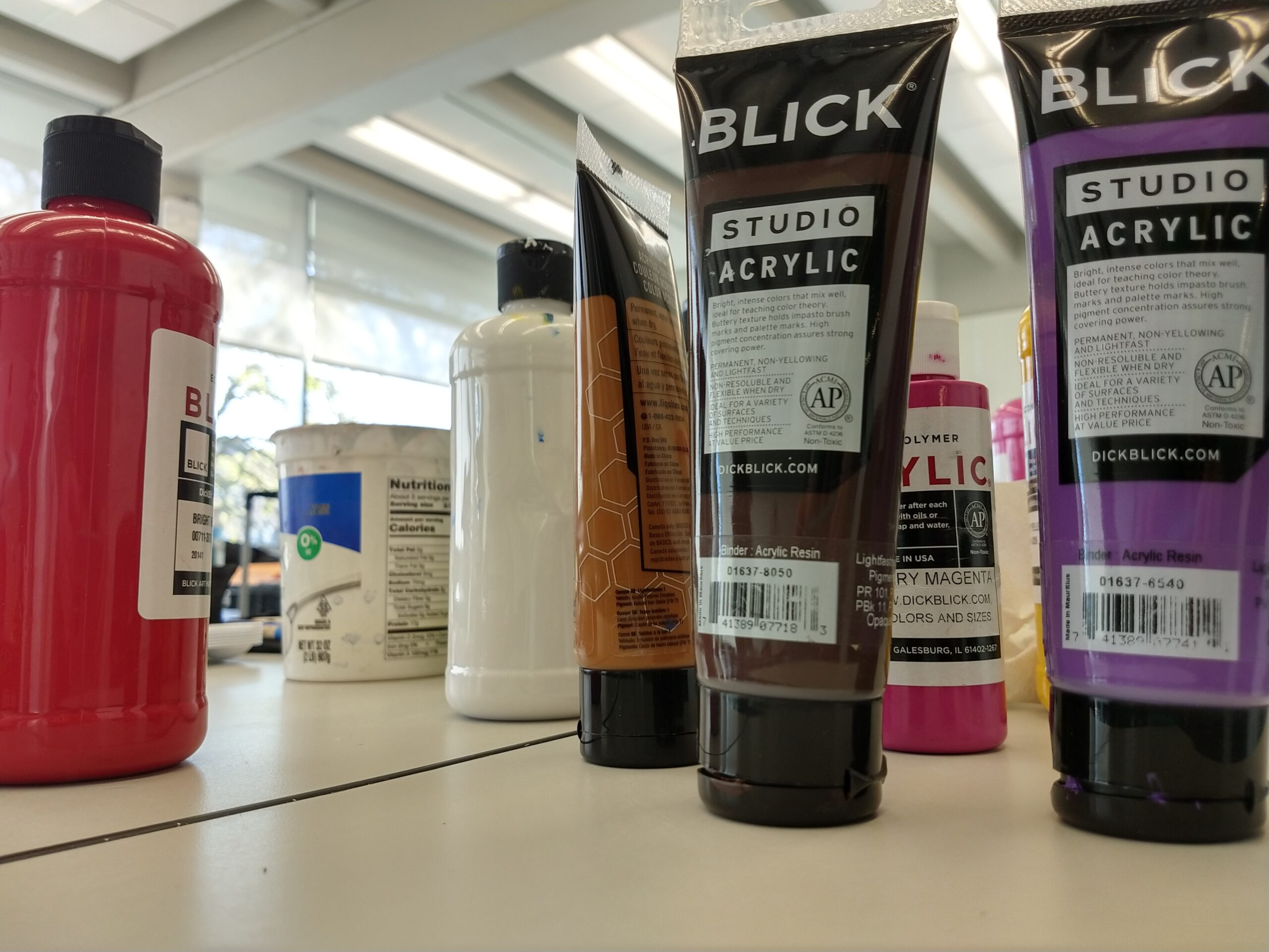 Image of acrlyic paint containers from the company Blick