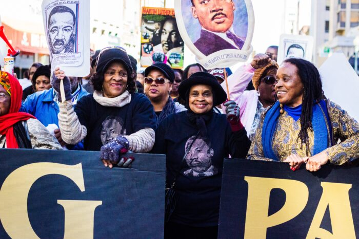 A group of African-American women smiling in the front of a crowd. The crowd behing is holding signs featuring images or Martin Luther King Jr.