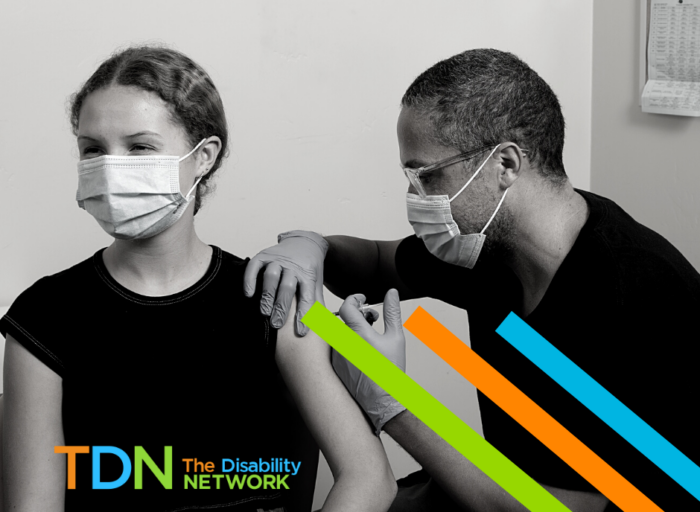 A black and white image of a woman recieving a vaccination in her upper left arm. Both people are wearing masks. There are three color blocks: green, orange, and blue across the bottom of the image and The Disability Network logo on the bottom right.