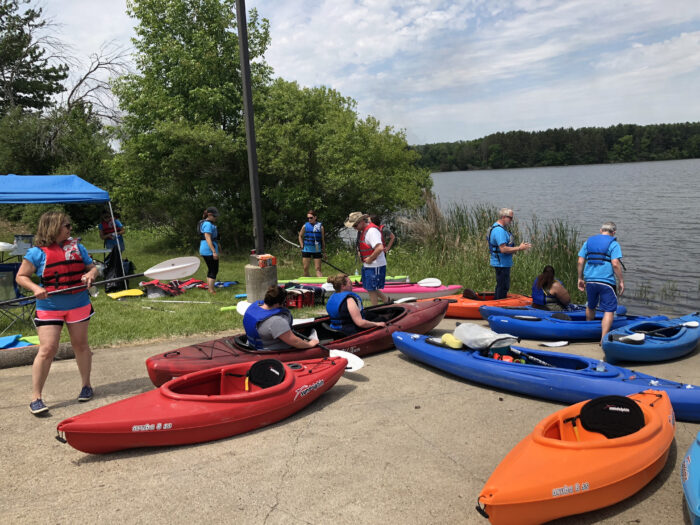 A group of volunteers and kayakers are preparing to launch onto a river. There are colorful kayaks all around as people get ready.