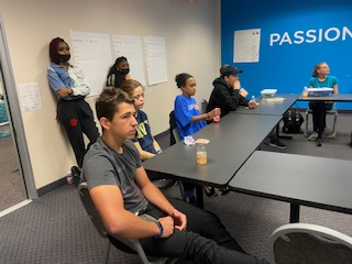 Students listen to an instructor in a conference room.